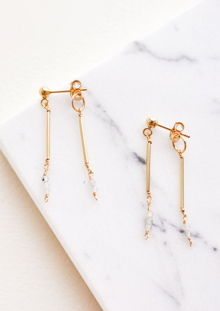 Two part dangling earrings featuring gold post and white beads hanging from each of the post and the earring back.