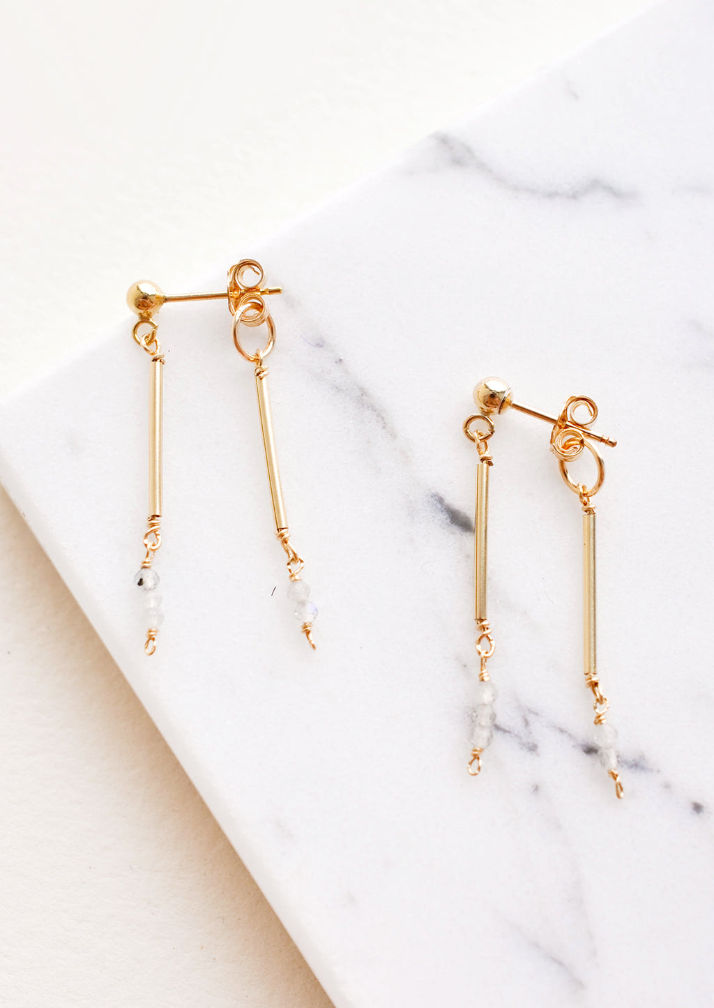 Moonstone: Two part dangling earrings featuring gold post and white beads hanging from each of the post and the earring back.