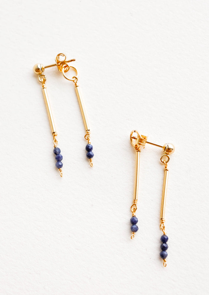Sapphire: Two part dangling earrings featuring gold post and blue beads hanging from each of the post and the earring back.