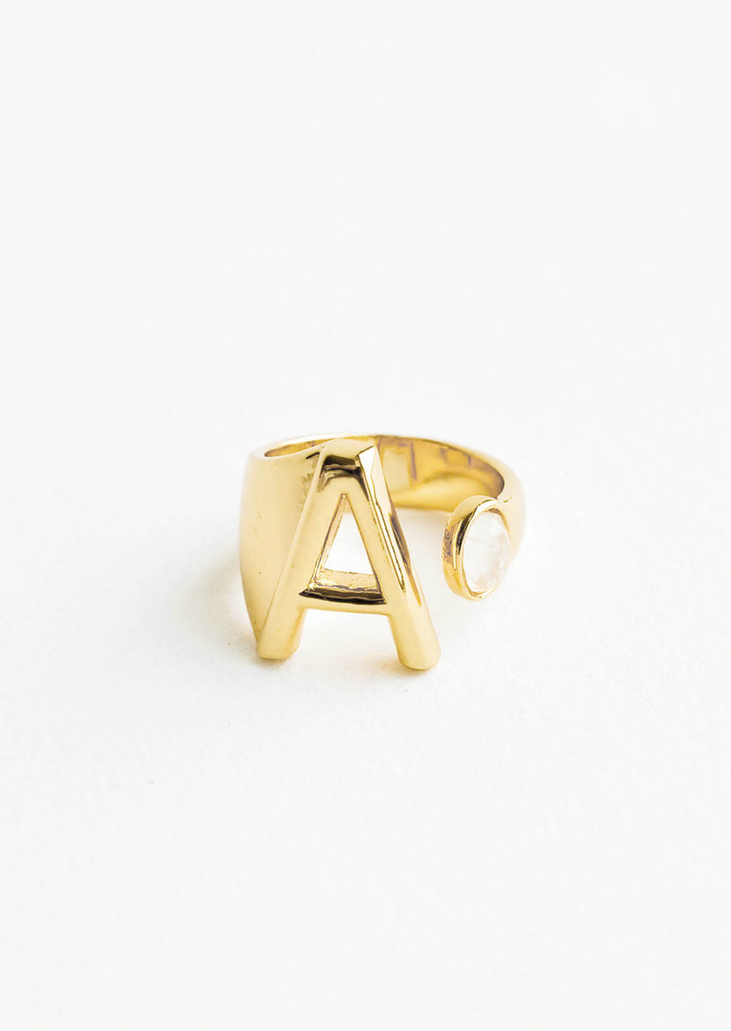 A: Yellow gold ring with letter A and oval glass crystal, and wide adjustable band.