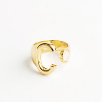 C: Yellow gold ring with letter C and oval glass crystal, and wide adjustable band.