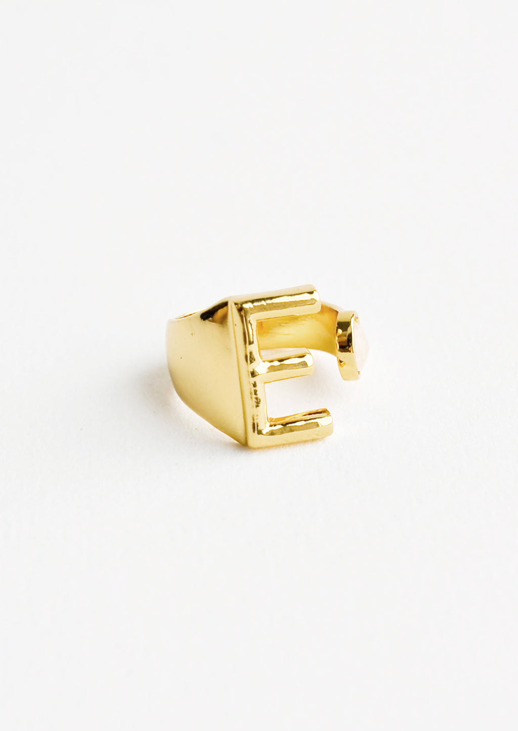 E: Yellow gold ring with letter E and oval glass crystal, and wide adjustable band.