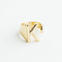 K: Yellow gold ring with letter K and oval glass crystal, and wide adjustable band.