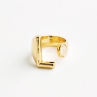 11: Yellow gold ring with letter L and oval glass crystal, and wide adjustable band.