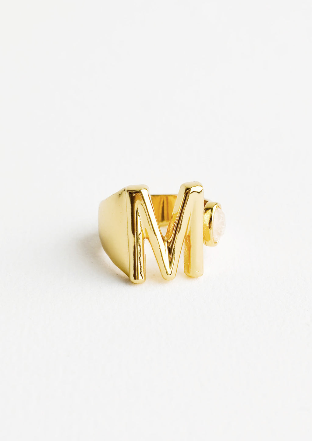 M: Yellow gold ring with letter M and oval glass crystal, and wide adjustable band.