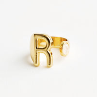 R: Yellow gold ring with letter R and oval glass crystal, and wide adjustable band.