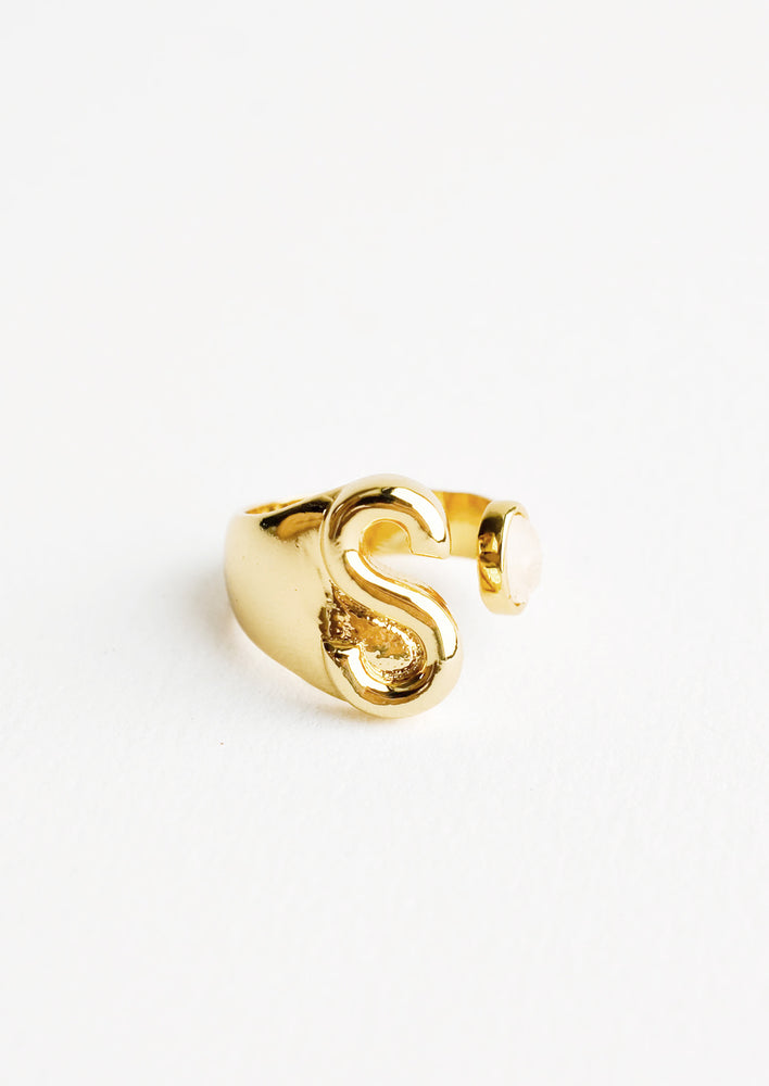 S: Yellow gold ring with letter S and oval glass crystal, and wide adjustable band.