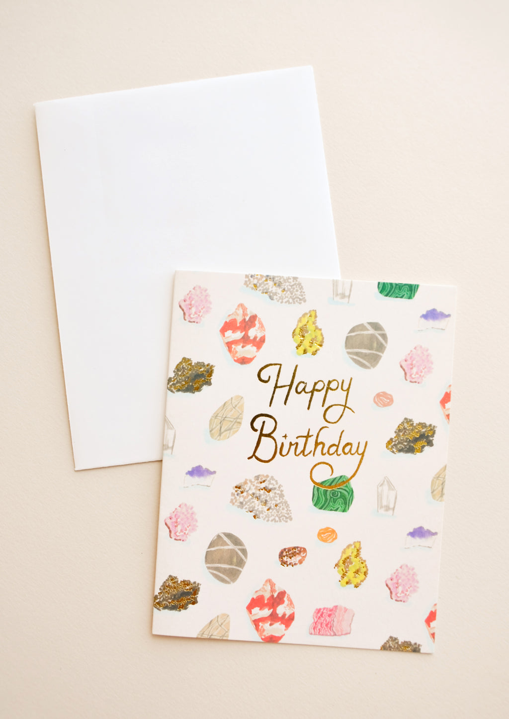 "1: Notecard with colorful drawings of gems and minerals and the text ""Happy Birthday"" in gold foil, with white envelope."
