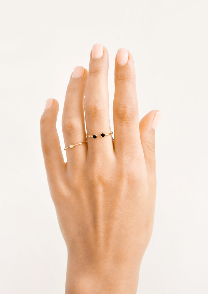 4: Model shot of hand wearing two gold rings with stones.