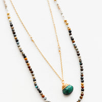 African Turquoise: A two-layer gold necklace with one strand of small, round multi-color stones and another of the thin gold chain and green gemstone pendant.