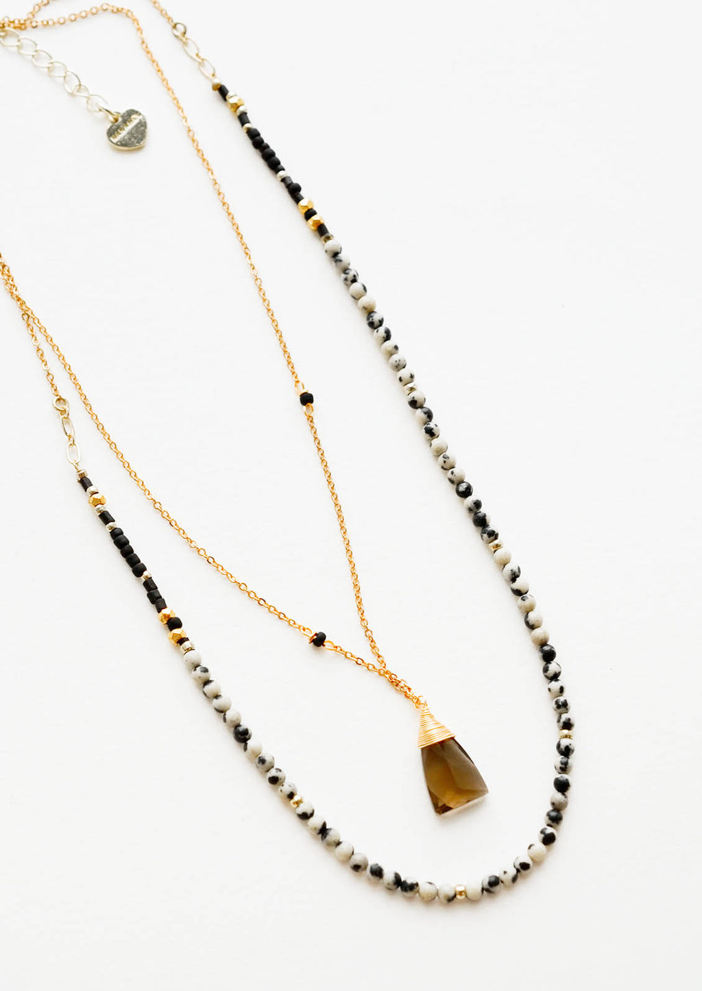 Dalmatian Jasper: A two-layer gold necklace with one strand of small, round cream and black stones and another of the thin gold chain and brown gemstone pendant.
