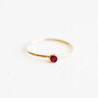 Garnet / Size 5: Yellow gold ring with slim band and small red garnet stone.