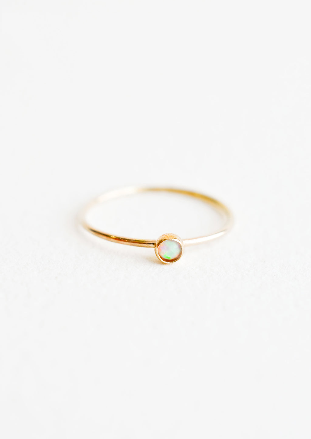 Opal / Size 5: Yellow gold ring with slim band and small white opal stone.