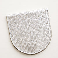 Metallic Silver: A metallic silver leather half-oval wallet with a subtle geometric pattern.