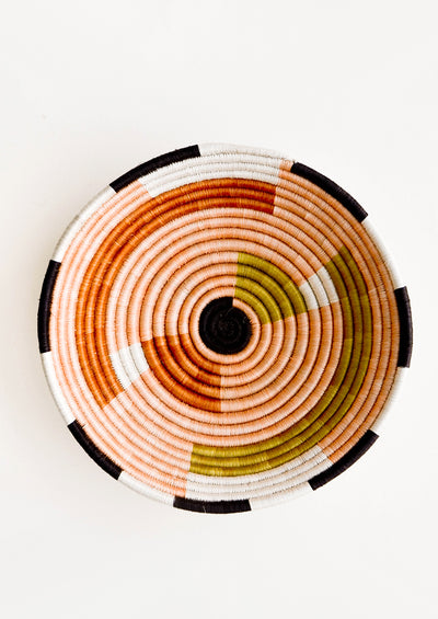 Round bowl made from woven sweetgrass, dyed in earthy colors with geometric pattern