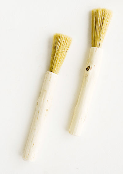 Hard-carved wooden pastry brush in long and skinny shape with bristle end