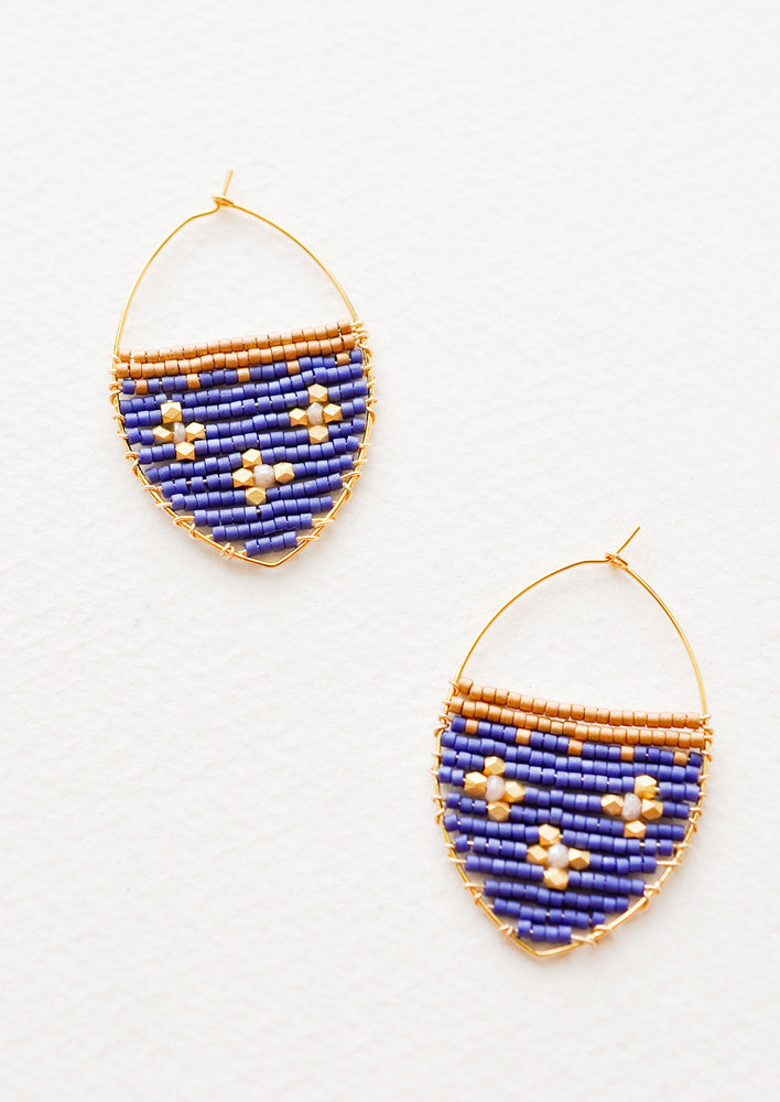 Regal Blue: Delicate gold drop earrings with a field of blue glass beads featuring three gold equal-armed cross designs.