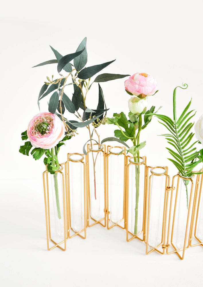 Brass: Multi-stem vase composed of nine glass vials side by side, resting inside individual compartments on a brass metal frame.