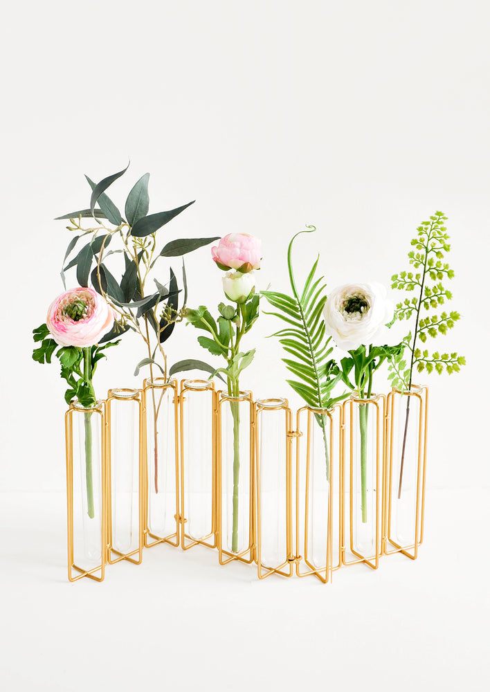 2: Multi-stem vase composed of nine glass vials side by side, resting inside individual compartments on a brass metal frame.