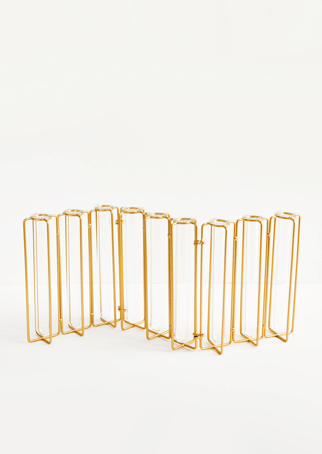 4: Multi-stem vase composed of nine glass vials side by side, resting inside individual compartments on a brass metal frame.