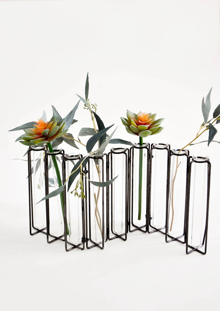 Multi-stem vase composed of nine glass vials side by side, resting inside individual compartments on a metal frame.