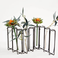 Iron: Multi-stem vase composed of nine glass vials side by side, resting inside individual compartments on a metal frame.