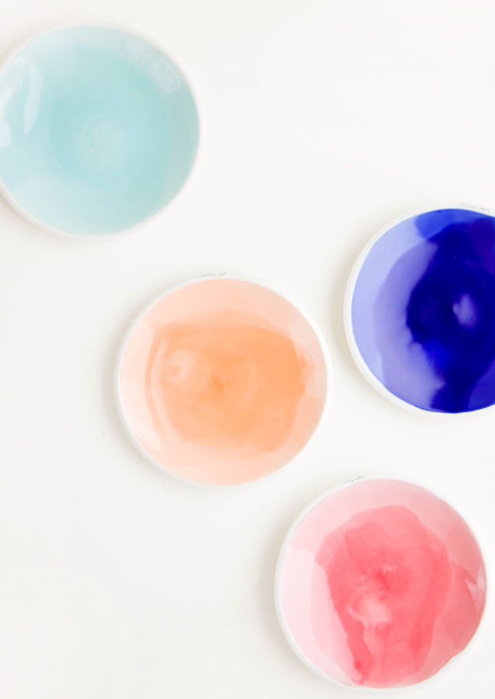 Medium: Four shallow porcelain dishes in light blue, dark blue, pale orange, and pink with shiny finishes and matte white rims.