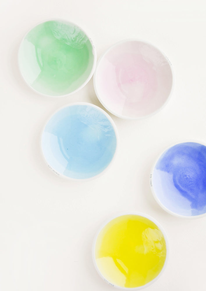 Five shallow porcelain dishes in light blue, blue, pale pink, green, and yellow with shiny finishes and matte white rims.