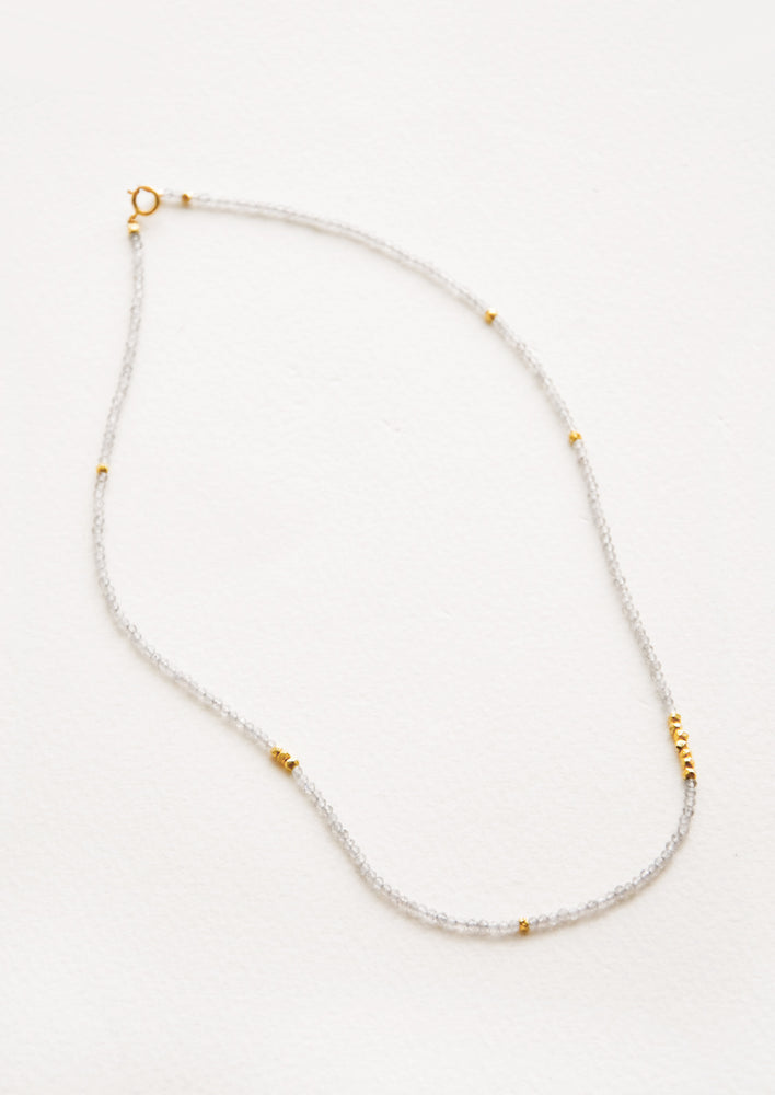 Labradorite: A necklace of pale gray gemstones, evenly spaced gold beads, and a gold clasp.