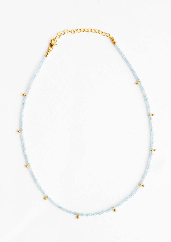 Aqua Chalcedony: A necklace of clear blue stones with evenly spaced gold beads and a golden chain clasp.