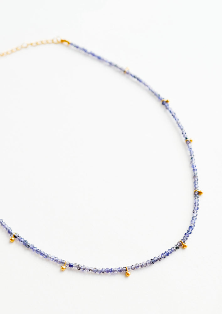 Iolite: A necklace of deep blue stones with evenly spaced gold beads and a golden chain clasp.