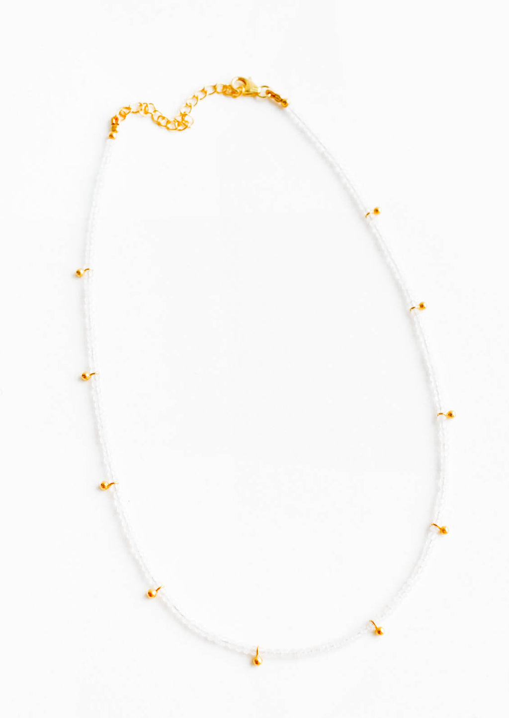 Moonstone: A necklace of clear gray gemstones with evenly spaced gold beads and a golden chain clasp.