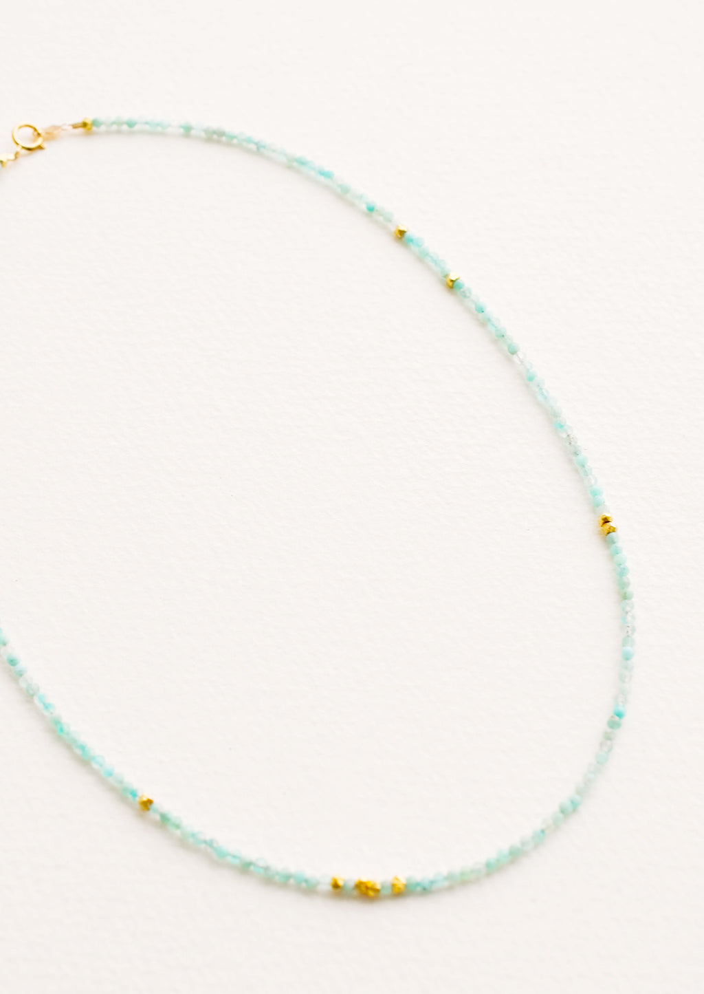 Aqua Chalcedony: A necklace of light blue gemstones, evenly spaced gold beads, and a gold clasp.