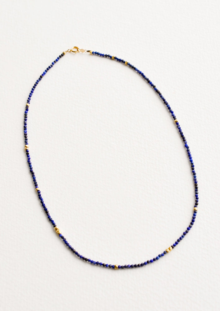 Lapis: A necklace of deep blue gemstones, evenly spaced gold beads, and a gold clasp.