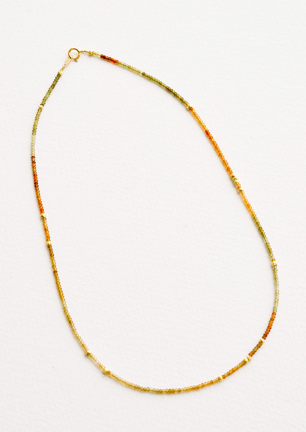 Tourmaline: A necklace of deep amber gemstones, evenly spaced gold beads, and a gold clasp.