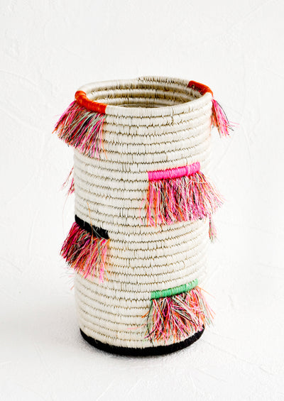 Tall cylindrical vase made from white woven sweetgrass with neon fringe throughout.