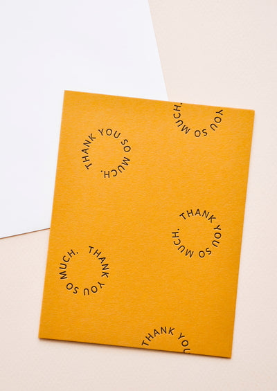 "Marigold notecard with the text ""Thank you so much"" set in a circle several times, with white envelope."