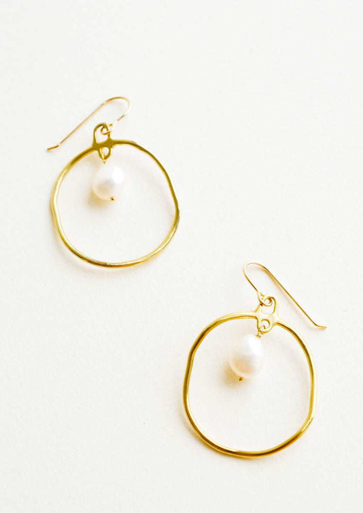 Brass: Circular drop earrings in gold with a small pearl dangling within.