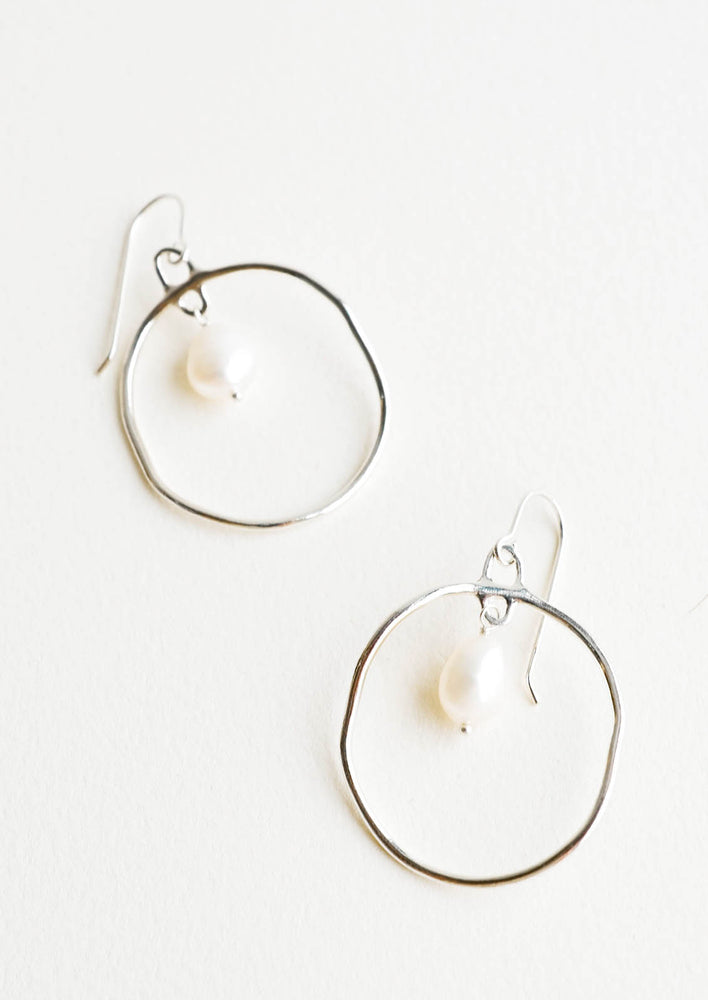 Sterling Silver: Circular drop earrings in silver with a small pearl dangling within.