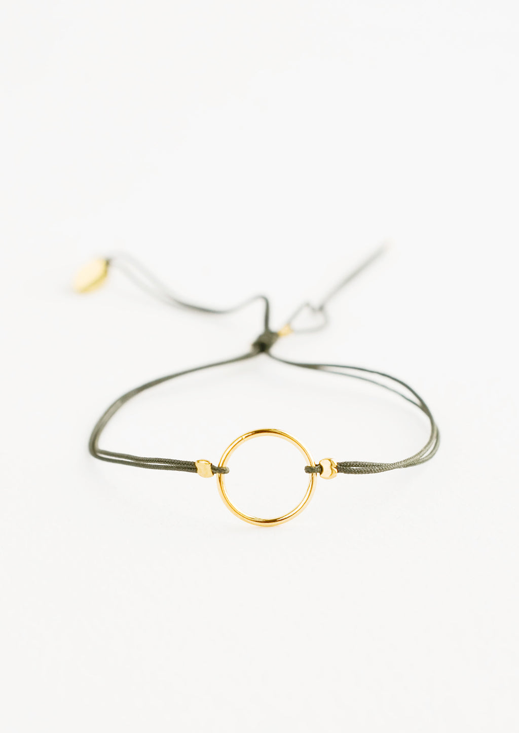 Khaki: Bracelet with yellow gold circle charm centered on an adjustable green string.