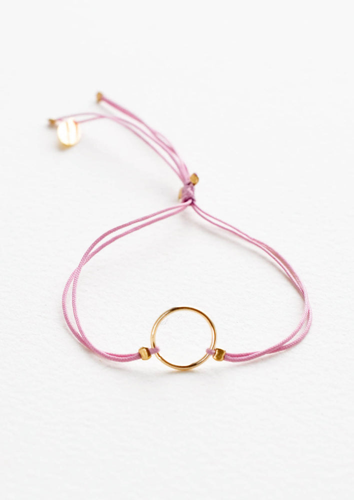 Orchid: Bracelet with yellow gold circle charm centered on an adjustable purple string.