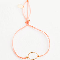 Peach: Bracelet with yellow gold circle charm centered on an adjustable peach string.