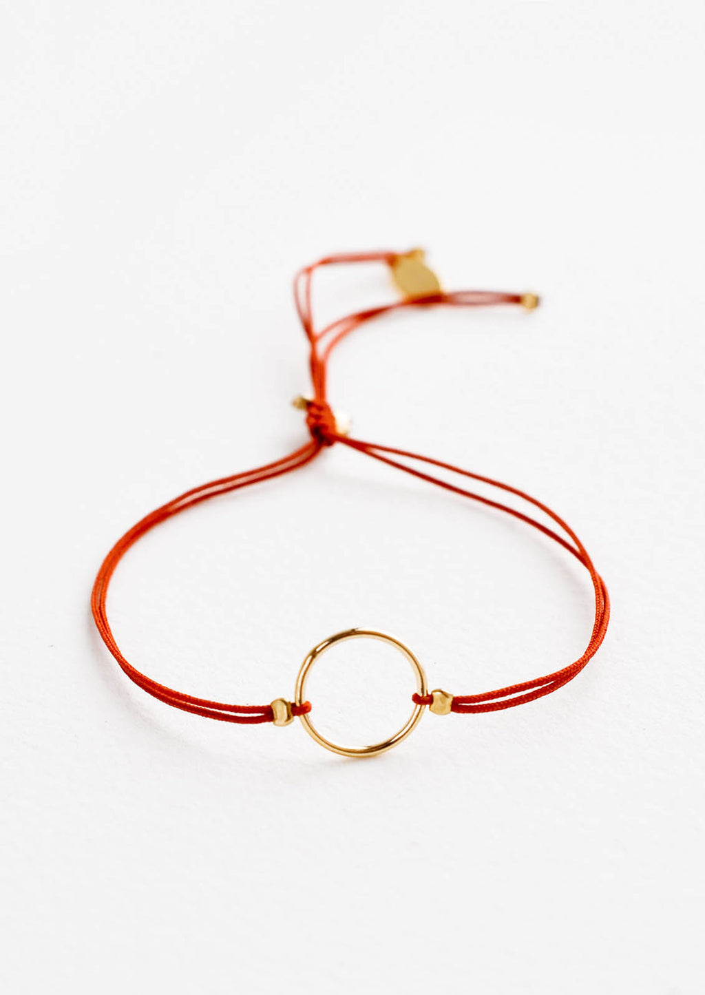 Rust: Bracelet with yellow gold circle charm centered on an adjustable red string.