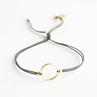 Charcoal: Bracelet with yellow gold circle charm centered on an adjustable dark grey string.