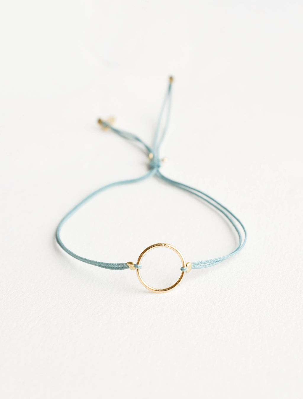 Teal: Bracelet with yellow gold circle charm centered on an adjustable teal string.
