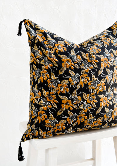 A square throw pillow in dark indigo with mustard floral print.
