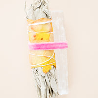 1: A dried sage bundle wrapped in yellow and pink dried rose petals alongside a rectangular white crystal both secured by a pink velvet ribbon.