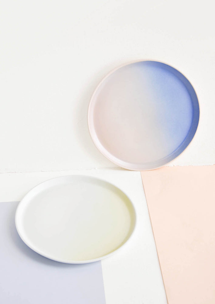 2: Two rimmed porcelain plates in blue and pink ombre and white and yellow ombre.