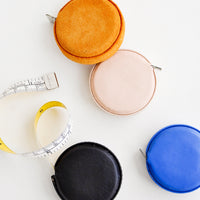 1: Product shot featuring multiple styles of leather covered tape measures.