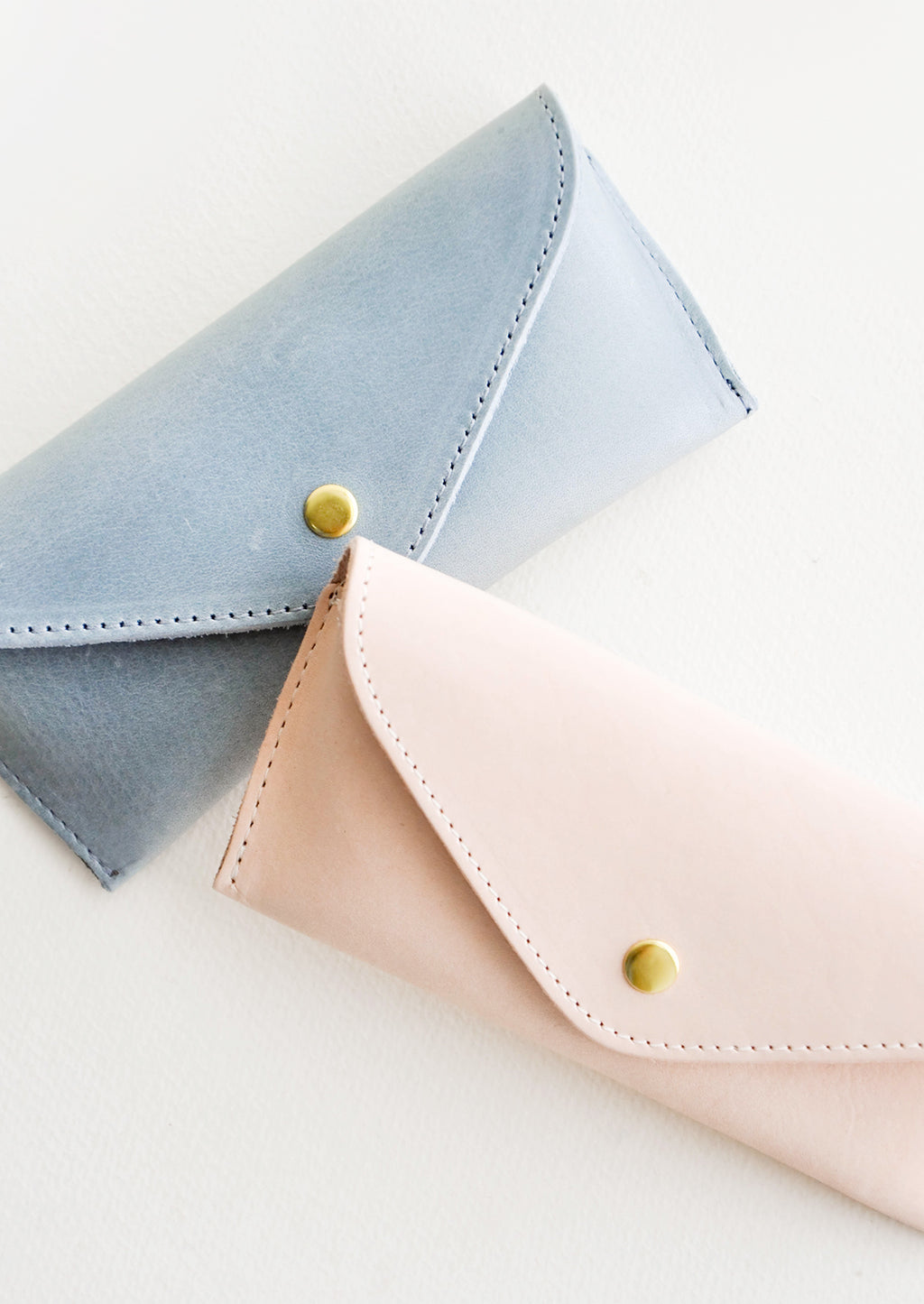 1: Two leather cases for sunglasses that fold close with a snap, one blue and one pink.
